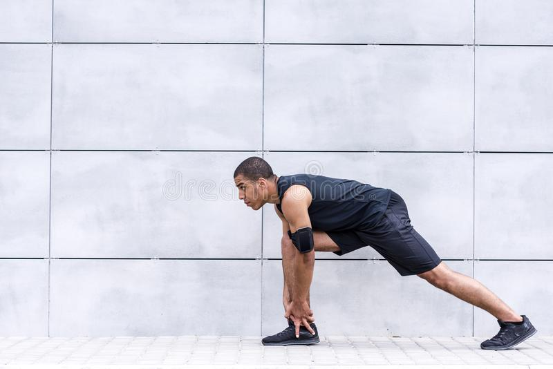 Afrikansk amerikanlöpare som sträcker på gatan arkivfoto