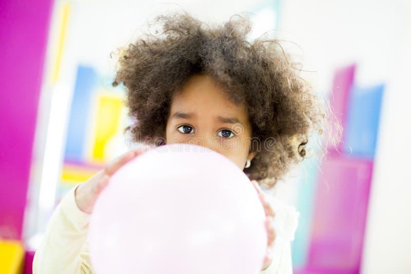 Afrikansk amerikanliten flicka med en ballong royaltyfri foto