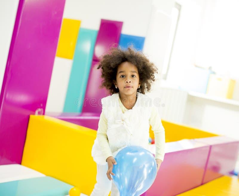 Afrikansk amerikanliten flicka med en ballong fotografering för bildbyråer