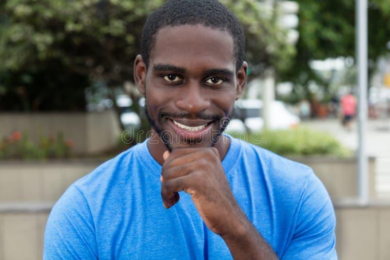 Afrikansk amerikanman med den blåa skjortan som ser kameran royaltyfria bilder