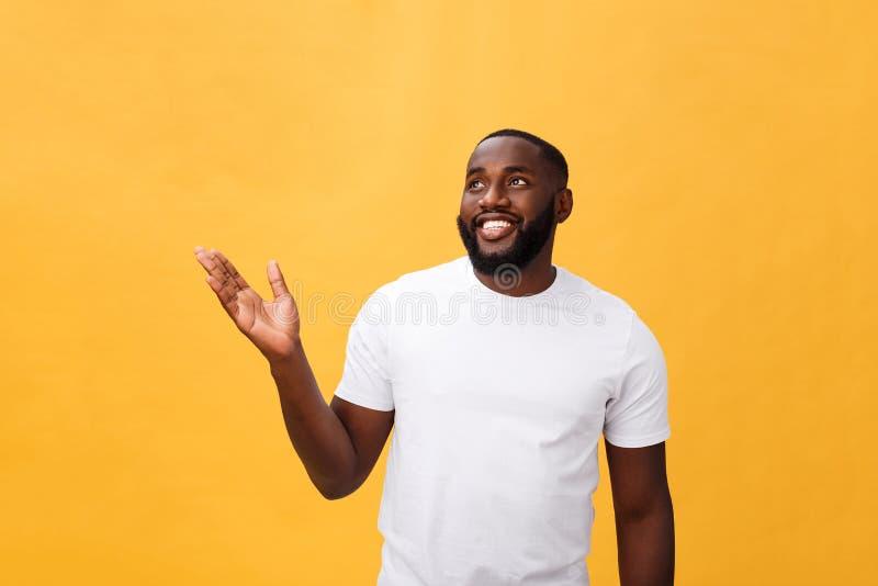 Afrikansk amerikanman med sidan för skäggvisninghand som bort isoleras över gul bakgrund arkivbilder