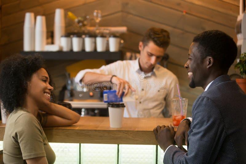 Afrikansk amerikanman och kvinna som flörtar samtal på coffeeshoplodisar arkivfoto