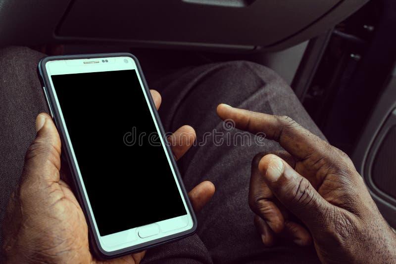 Afrikansk amerikanman som använder den mobila smarta telefonen med den tomma svarta skärmen Falskt upp av en svart maninnehavappa royaltyfri bild
