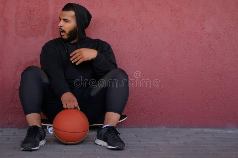 Afrikansk amerikanman som bär en svart hoodie som sitter på en skateboard med en basket, från sidan gäspar och ser royaltyfri foto