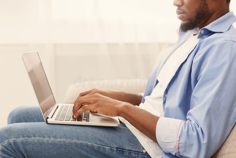 Afrikansk amerikanman som bl?ddrar arbetstillf?llen p? b?rbara datorn arkivfoto
