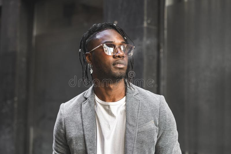Afrikansk amerikanman som röker en cigarr i gatan Stil för svart grabb arkivbilder