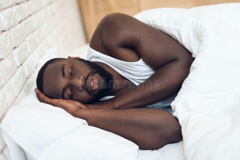 Afrikansk amerikanman som sover i säng arkivfoton