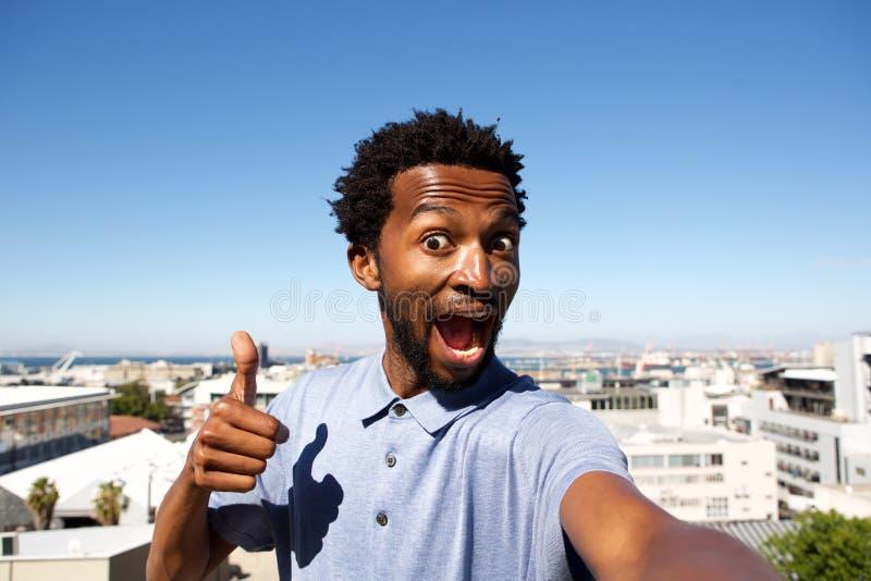 Afrikansk amerikanmananseende vid stads- bakgrund med tummen upp royaltyfri bild