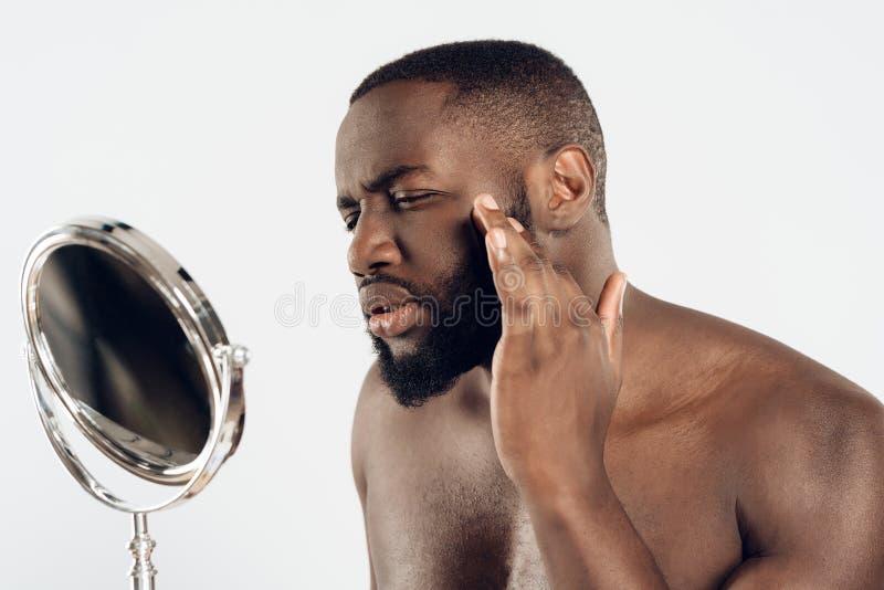Afrikansk amerikanmanbruk som fuktar lotion arkivfoto