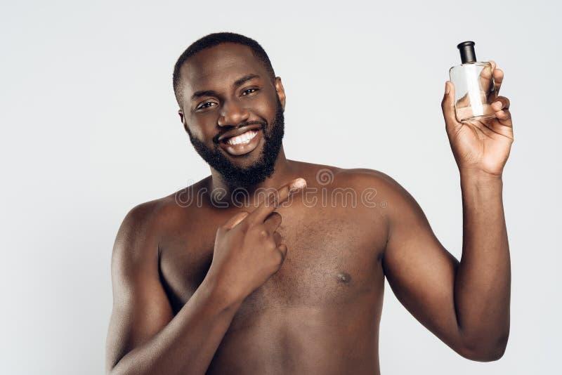Afrikansk amerikanmannen använder rakvatten royaltyfri foto