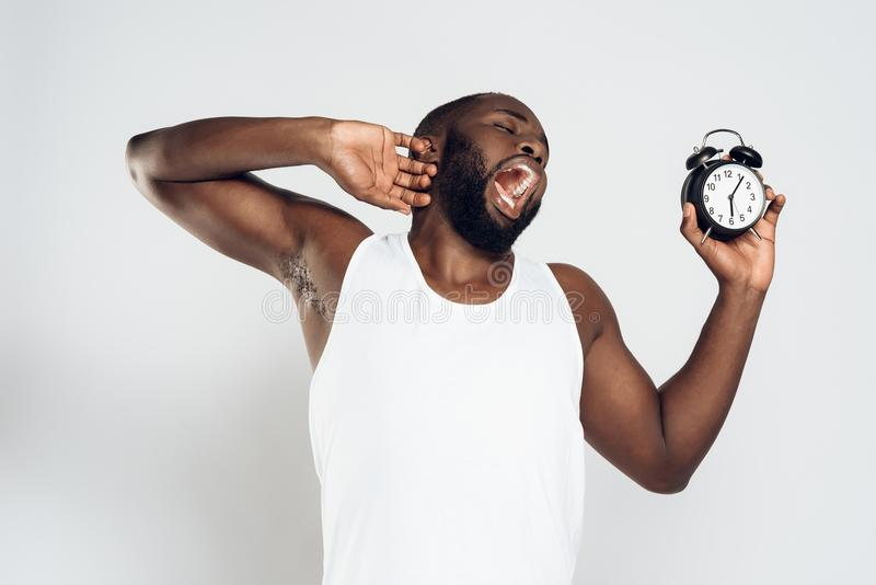 Afrikansk amerikanmannen gäspar den hållande ringklockan royaltyfri fotografi
