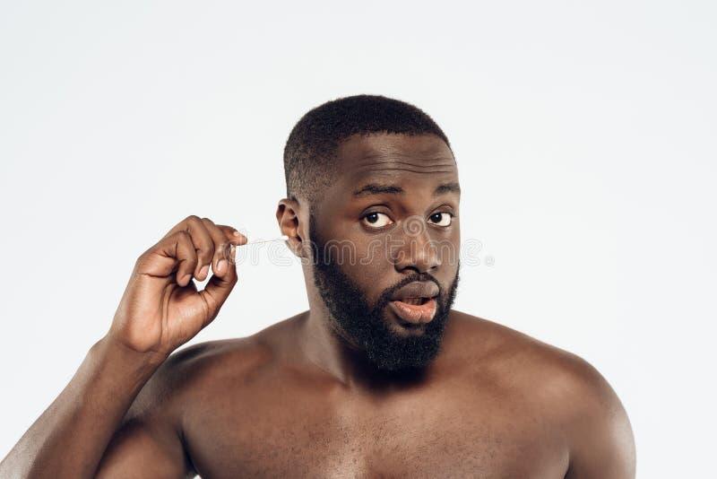 Afrikansk amerikanmannen gör ren öron royaltyfri bild