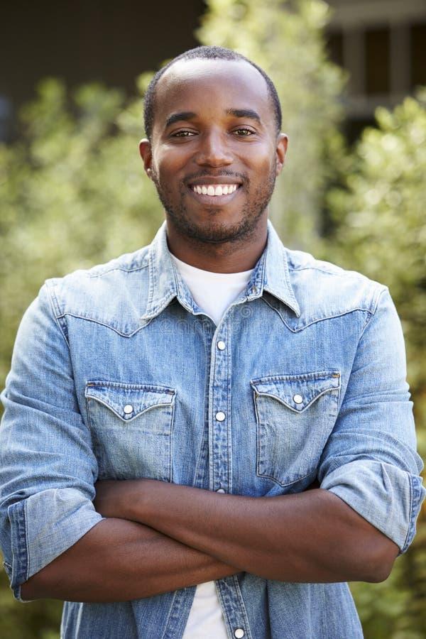 Afrikansk amerikanmannen i grov bomullstvillskjortan, armar korsade, lodlinjen fotografering för bildbyråer