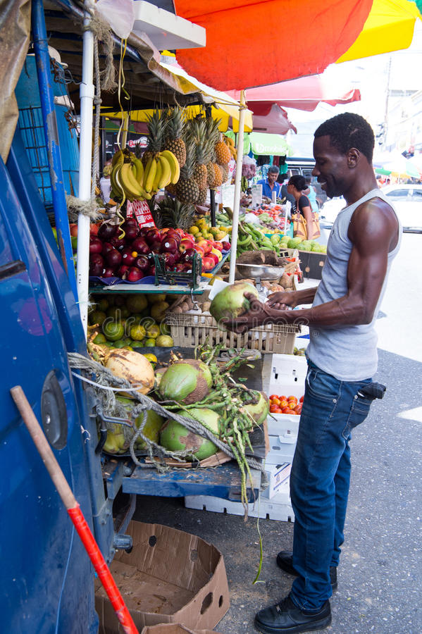 Afrikansk amerikanmannen köper kokosnötter royaltyfri fotografi