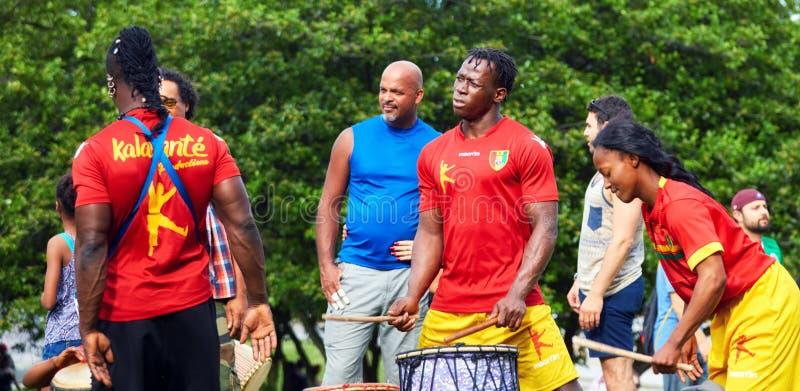 Afrikansk amerikanmannen och kvinnliga percussionists som spelar djembe- och dununvalsar på den Tam Tams festivalen i monteringsk arkivbild