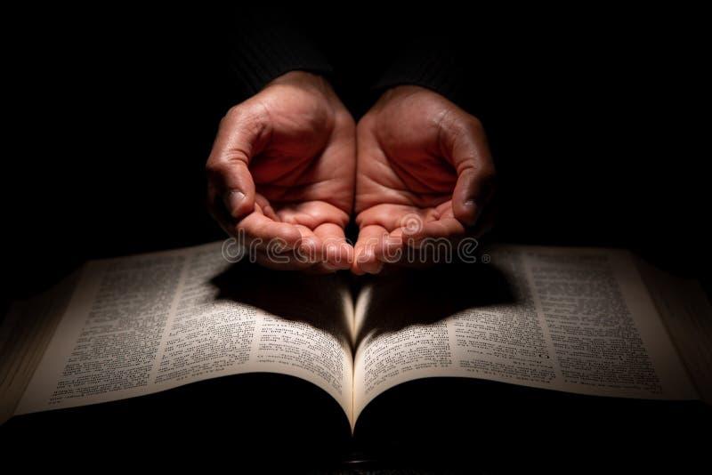 Afrikansk amerikanmannen som ber med händer, öppnar överst av bibeln royaltyfri fotografi