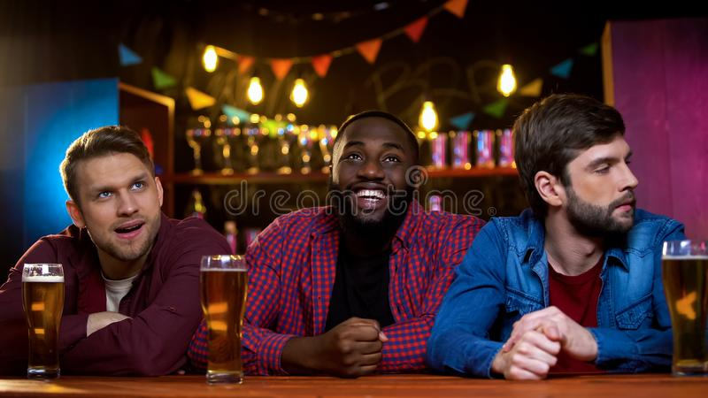 Afrikansk amerikanmannen som ler hållande ögonen på tv i stång, caucasian vänner, förargar royaltyfria bilder