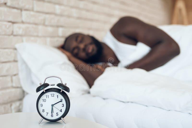 Afrikansk amerikanmannen sover i säng arkivbilder