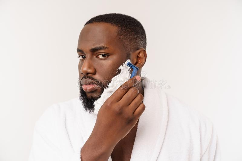 Afrikansk amerikanmannen suddar att raka kr?m p? framsida, genom att raka borsten Male hygien bakgrund isolerad white studio royaltyfri fotografi