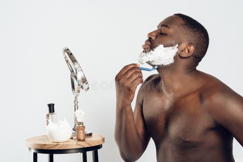 Afrikansk amerikanmansudd som rakar kräm arkivbilder