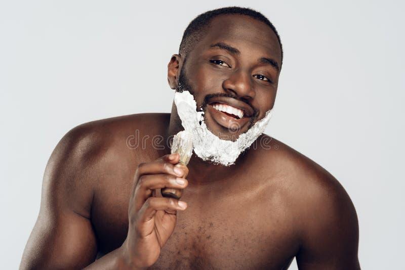 Afrikansk amerikanmansudd som rakar kräm arkivfoton