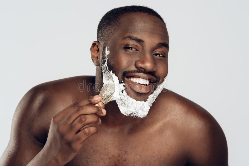 Afrikansk amerikanmansudd som rakar kräm fotografering för bildbyråer