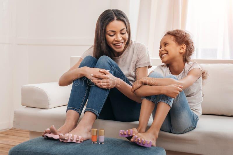 Afrikansk amerikanmoder och dotter som tillsammans gör pedikyr hemma royaltyfri fotografi
