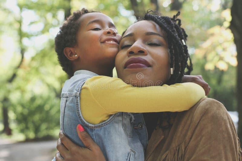 Afrikansk amerikanmoder som kramar hennes lilla dotter i äng royaltyfria foton