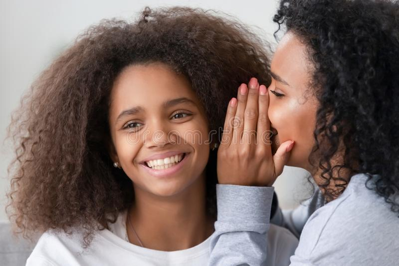 Afrikansk amerikanmoder som viskar till att le det tonåriga dotterörat fotografering för bildbyråer