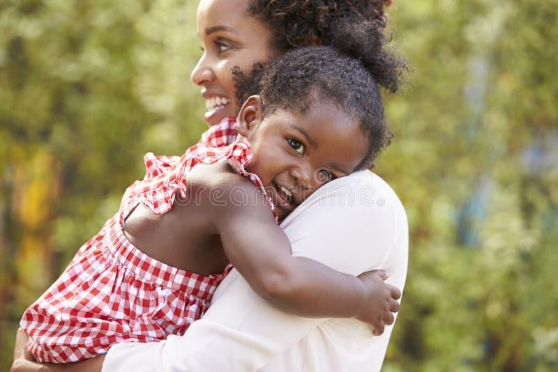 Afrikansk amerikanmodern som omfamnar med, behandla som ett barn dottern royaltyfri bild