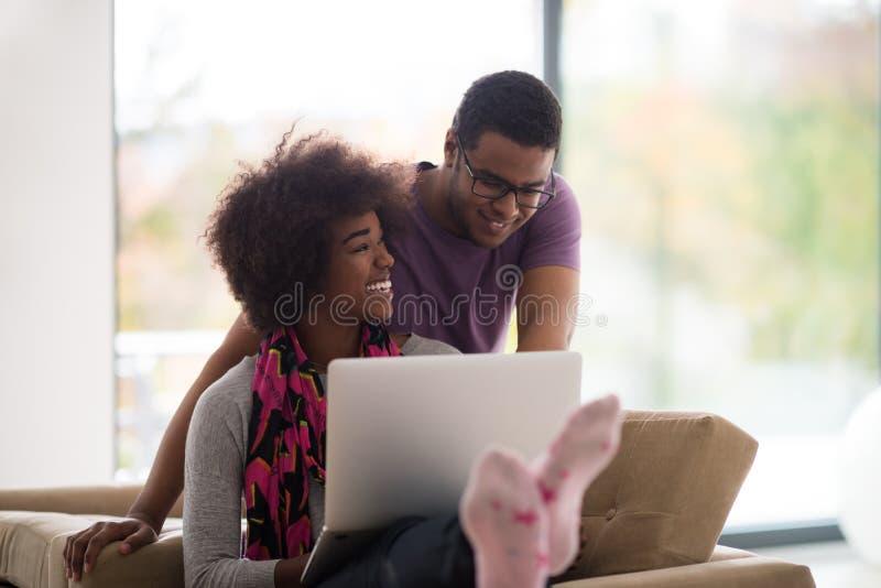 Afrikansk amerikanpar som direktanslutet shoppar fotografering för bildbyråer
