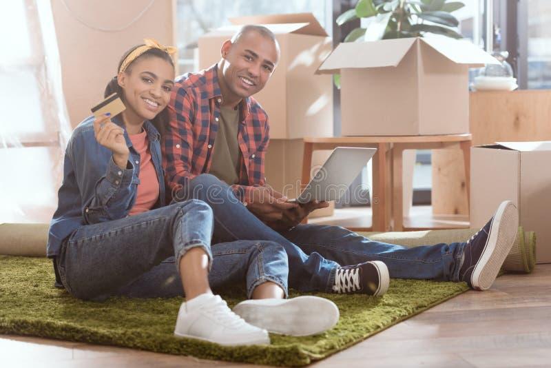 afrikansk amerikanpar som direktanslutet shoppar med kreditkorten och bärbara datorn i ny lägenhet arkivfoton