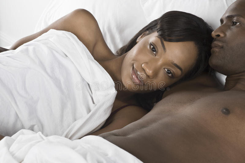 Afrikansk amerikanpar som ligger i säng arkivbild