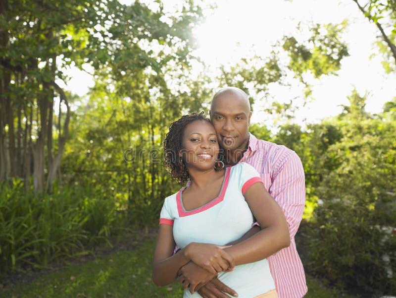 Afrikansk amerikanpar som omfamnar i trädgård royaltyfri bild