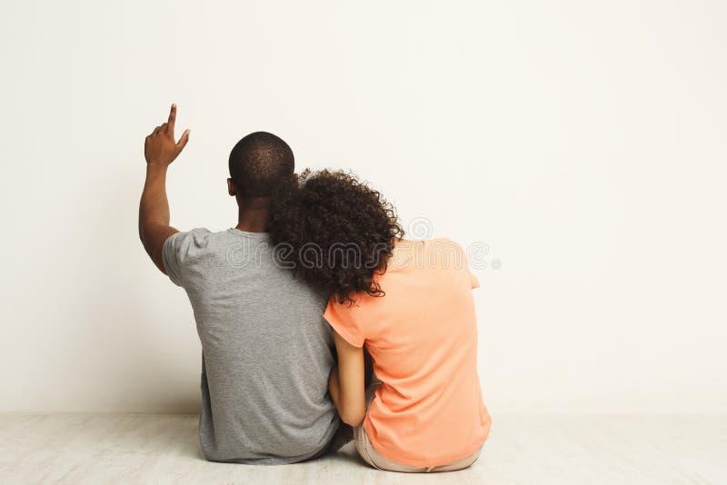 Afrikansk amerikanpar som ser upp och att sitta på golv royaltyfria bilder