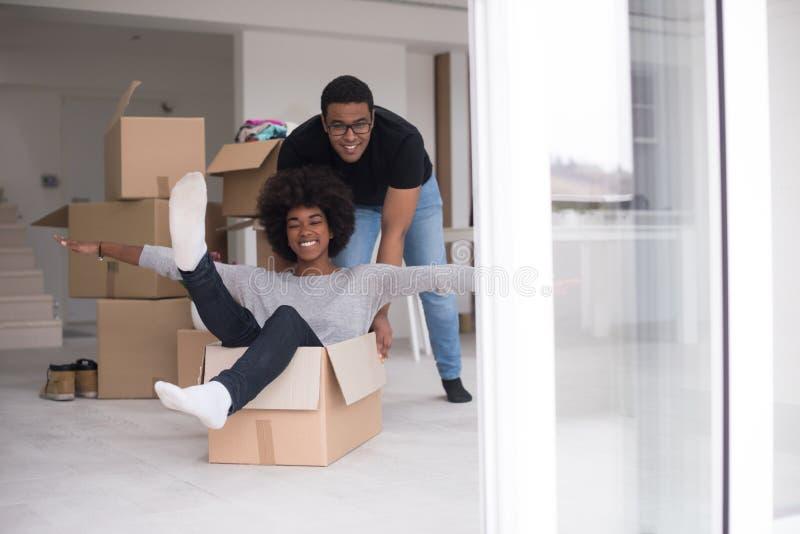 Afrikansk amerikanpar som spelar med emballagematerial royaltyfri fotografi