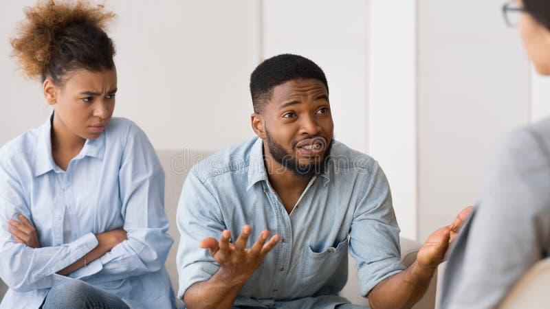 Afrikansk amerikanpar som talar till psykologen During Therapy Session arkivfoton