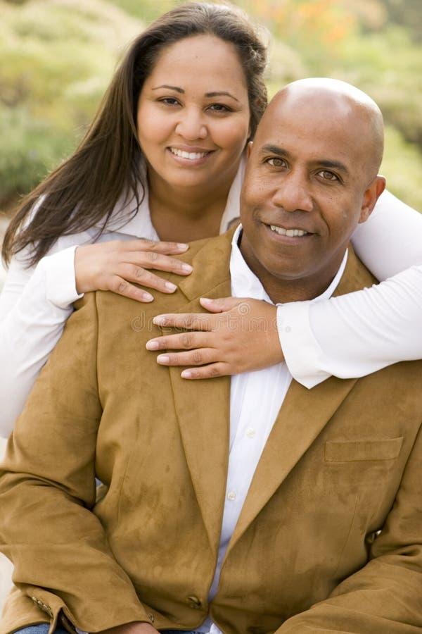 Afrikansk amerikanpar som utanför skrattar och kramar arkivfoton