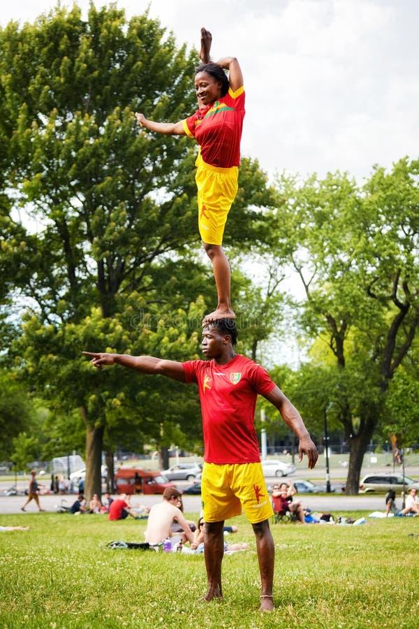 Afrikansk amerikanpar som utför akrobatik, visar av åhörarna i monteringskunglig person parkerar framme royaltyfri bild