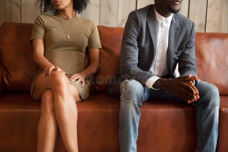 Afrikansk amerikanparsammanträde på soffan efter grälar, dåligt verkligt arkivbilder