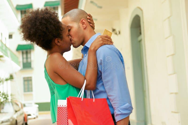 Afrikansk amerikanparshopping med att kyssa för kreditkort arkivbild