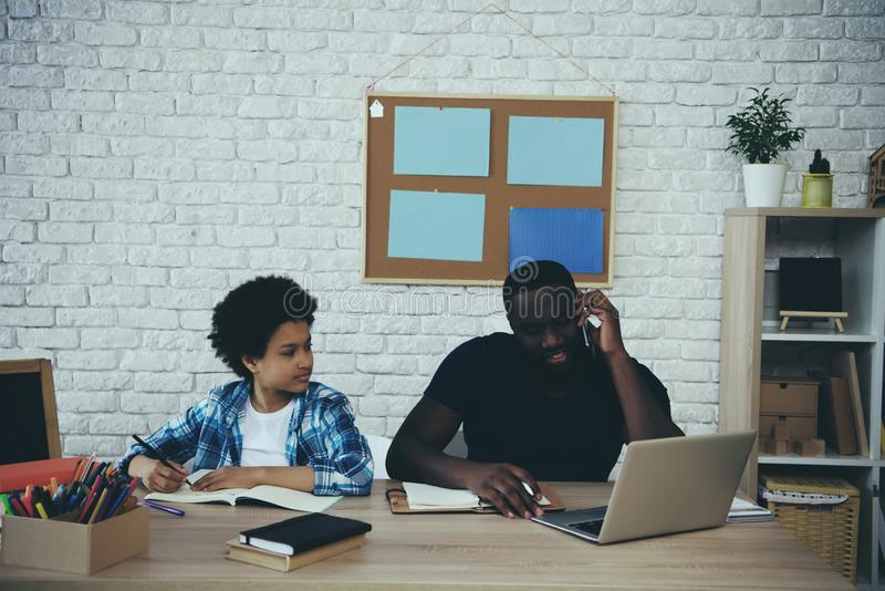 Afrikansk amerikanpojke som gör läxa när fader royaltyfri fotografi