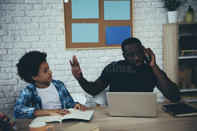 Afrikansk amerikanpojken distraherar fadern från arbete royaltyfria bilder