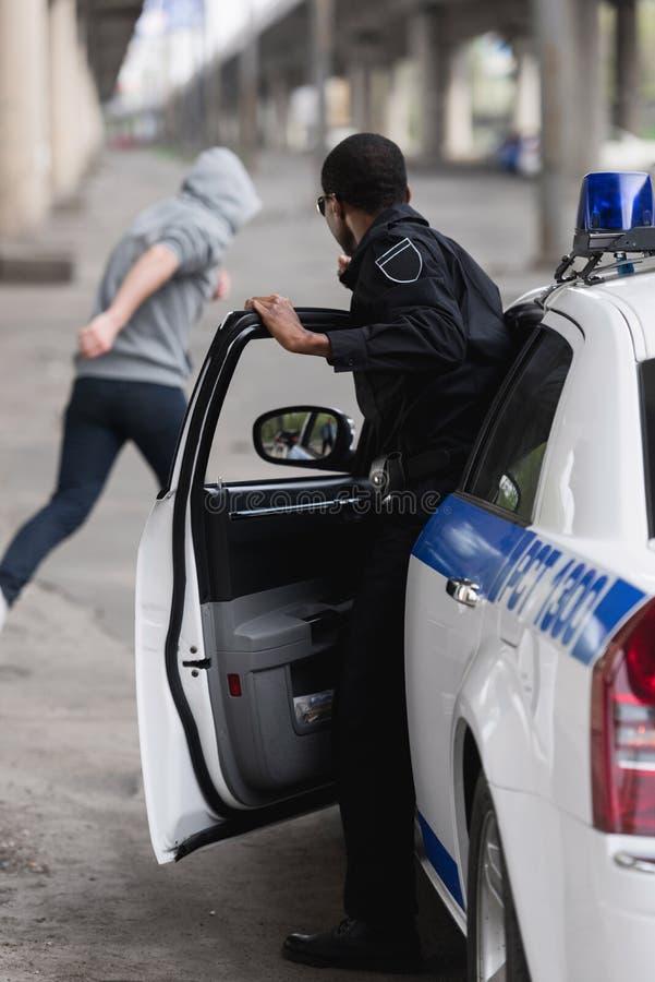 afrikansk amerikanpolis som får ut ur bilen royaltyfri bild
