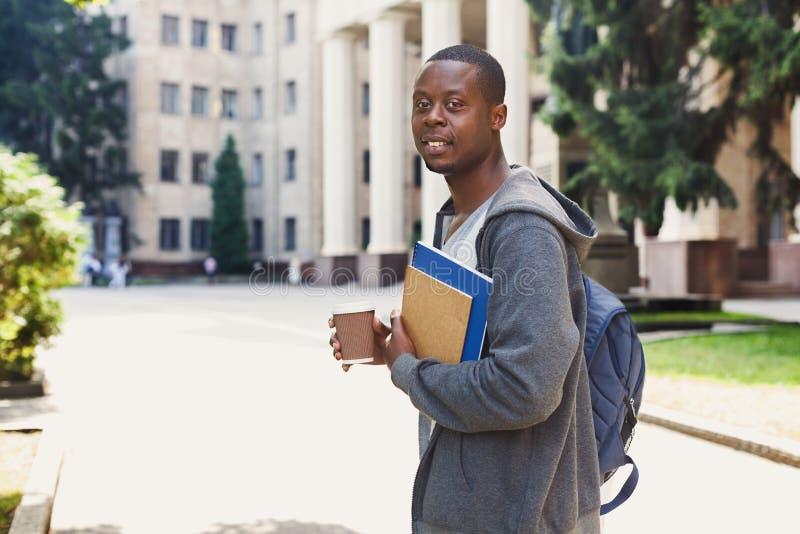 Afrikansk amerikanstudent med böcker i den utomhus- universitetsområdet royaltyfria foton