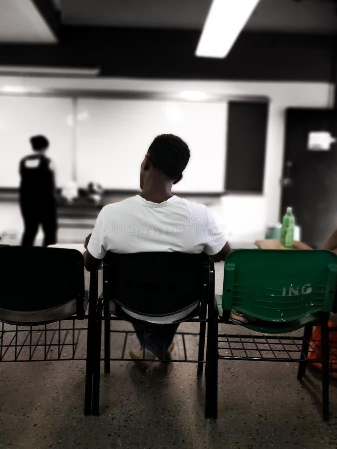 Afrikansk amerikanstudent som lyssnar till en grupp i ett skolaklassrum royaltyfri bild