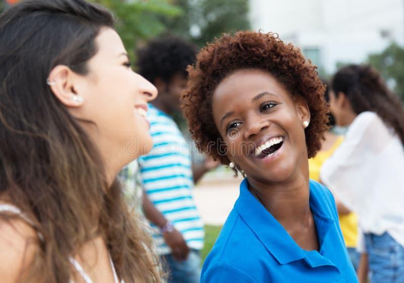 Afrikansk amerikanstudent som talar med den unga caucasian kvinnan på c royaltyfri bild