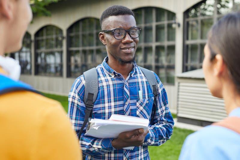 Afrikansk amerikanstudent Talking till vänner utomhus arkivfoto