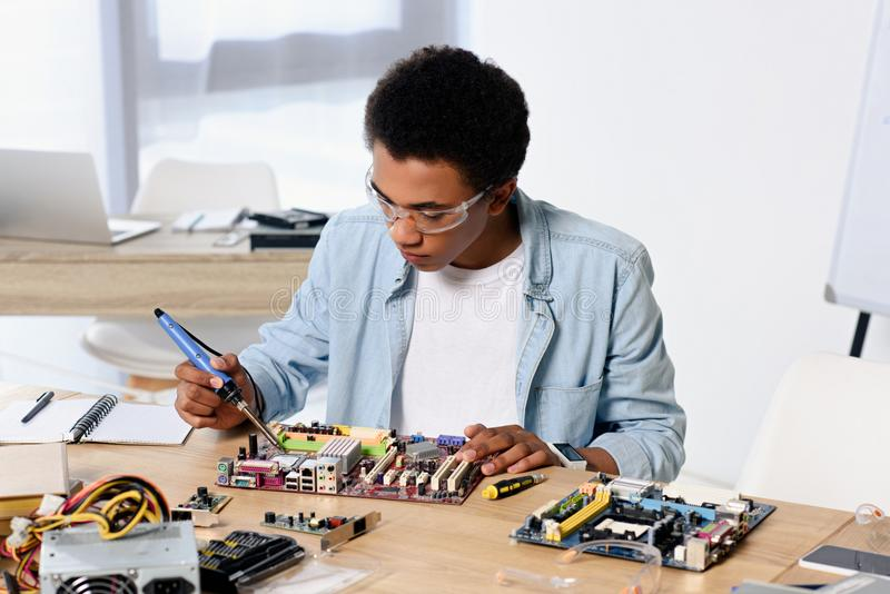 afrikansk amerikantonåring som löder datorströmkretsen med lödkolv arkivfoton