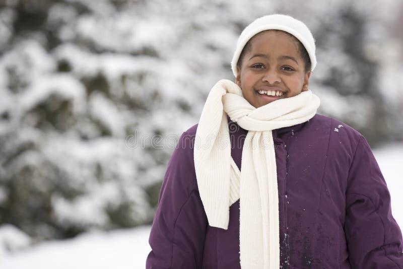 Afrikansk amerikanung flicka som ler i snön fotografering för bildbyråer